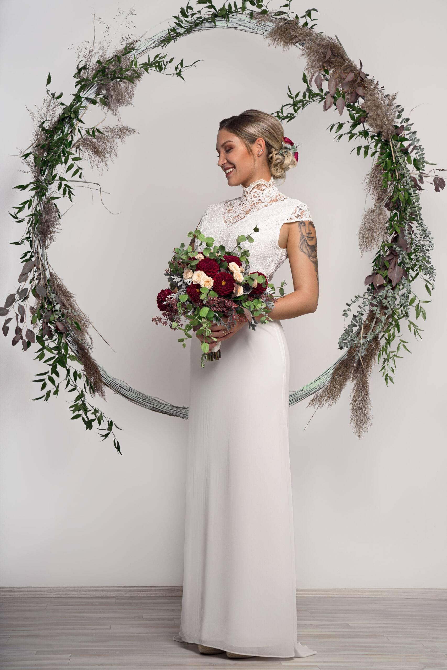 Gestylte Braut vor Traubogen
